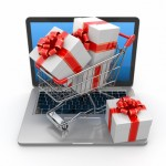 E-commerce. Shopping cart and gifts on laptop